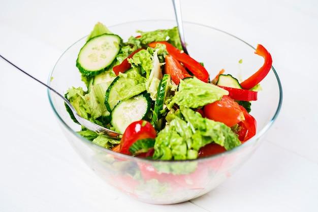 Alimentation saine, nourriture végétarienne, régime et concept de personnes - gros plan sur une salade de légumes à l'huile d'olive sur fond blanc