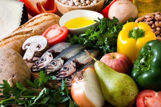 Alimentation saine. régime méditerranéen fruits, légumes, céréales, noix huile d'olive et poisson sur table en bois