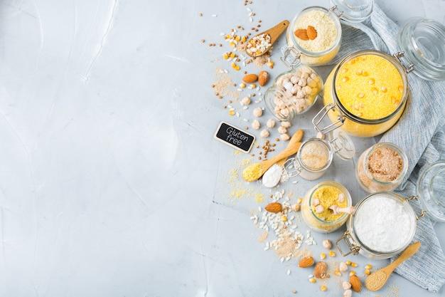 Alimentation saine, régimes amaigrissants, concept alimentaire équilibré. assortiment de farine sans gluten, amande, maïs, riz sur une table de cuisine. vue de dessus fond plat