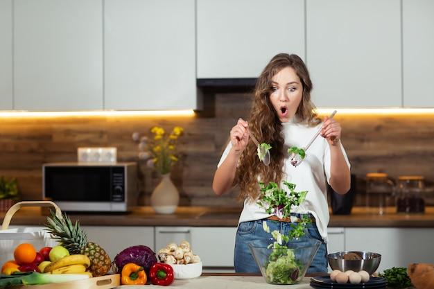 Alimentation saine - salade de légumes. régime. concept de régime. jeune femme bouclée prépare une salade de légumes dans sa cuisine. concept de mode de vie sain, belle femme émotive, surprise, mélange de légumes.