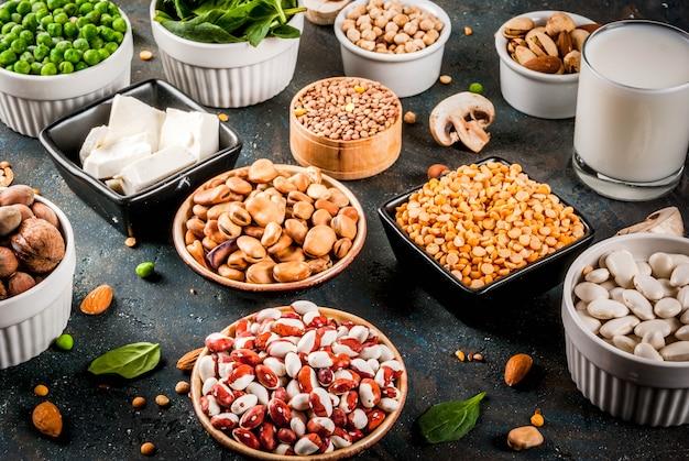 Alimentation végétalienne saine, sources de protéines végétales: tofu, lait végétalien, haricots, lentilles, noix, lait de soja, épinards et graines. vue de dessus sur tableau blanc.