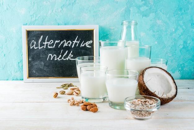 Aliments alternatifs végétaliens, ensemble de divers lait non laitiers - riz, noix de coco, amandes, pistache, sésame, graines de citrouille, soja, noix, flocons d'avoine, sur fond bleu clair, espace copie