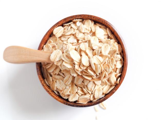 Aliments à base de grains de céréales avec flocons d'avoine séchée au four, flocons d'avoine dans une cuillère et un bol en bois