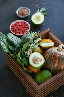 Aliments biologiques fermiers sains dans une boîte en bois : fruits, légumes, graines, superaliments, légumes-feuilles sur fond noir. concept de sélection de nourriture propre
