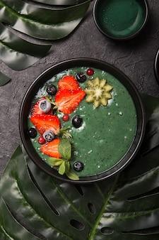 Aliments colorés et sains. bol à smoothie à l'açai. idée de petit déjeuner céto. smoothie aux fruits, acai. petit déjeuner avec spiruline verte, fraise, chia, kiwi en plaque noire