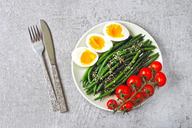 Aliments colorés et sains. flatlay. bol de bouddha avec des œufs, des haricots verts et des tomates cerises.