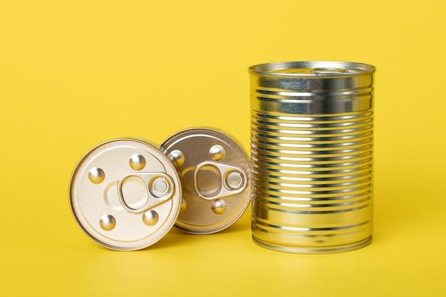 Aliments en conserve sur un mur jaune, boîtes dorées brillantes fermées. produits en conserve. bocaux métalliques. préserve, conserve.