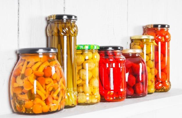 Aliments conservés dans des bocaux en verre, sur une étagère en bois. divers aliments marinés