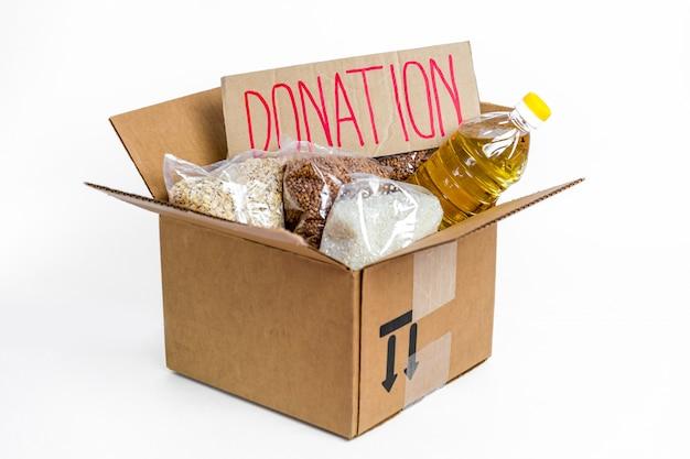 Aliments dans une boîte de dons en carton, isolé sur fond blanc. stock anti-crise de biens essentiels pour la période d'isolement en quarantaine. livraison de nourriture, coronavirus. pénurie de nourriture. signer avec du texte.