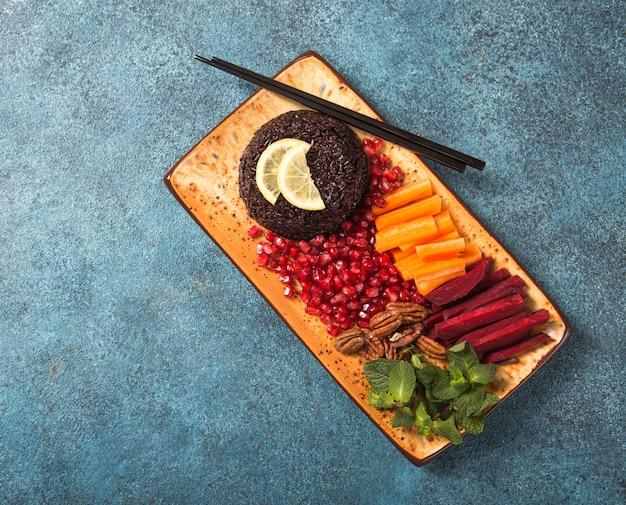 Aliments diététiques thaïlandais, riz noir cuit avec carotte crue, betterave, noix de pécan, grenade et menthe. bol végétalien sain. vue de dessus avec espace copie.