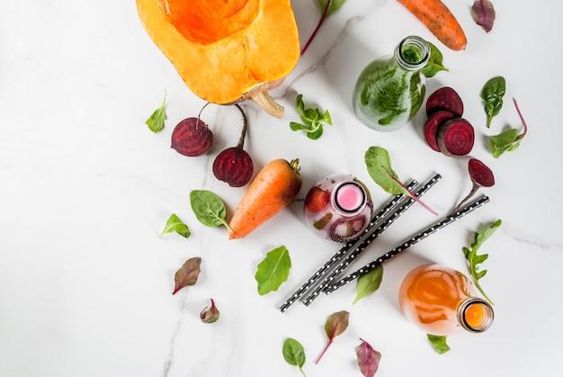 Aliments diététiques végétaliens. boissons smoothies fraîches bio sélectionnées avec des légumes d'automne: betterave rouge, citrouille, carotte, légumes à feuilles. en bouteilles, tableau blanc. copier la vue de dessus de l'espace