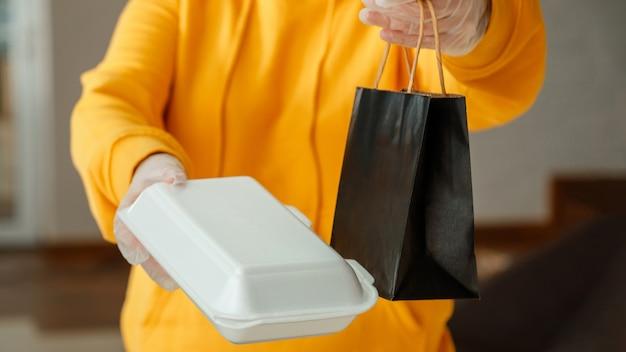 Aliments à emporter sac en papier contenant en polystyrène sac de nourriture déjeuner maquette paquet à emporter dans le restaurant à emporter employé de cuisine émet des commandes en ligne dans des gants livraison de nourriture sans contact longue bannière web