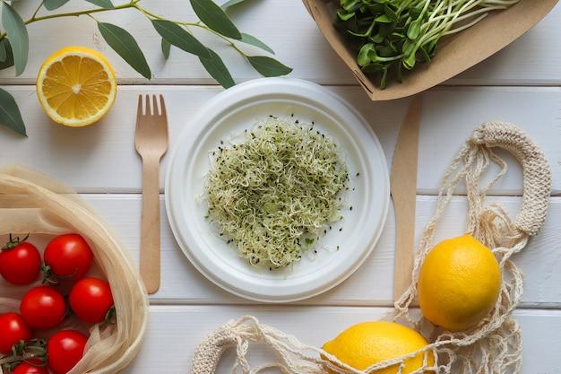 Aliments frais dans un ustensile biologique jetable écologique. microgreen, tomates et citrons sur table en bois
