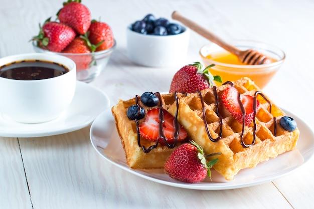 Aliments frais faits maison de gaufres belges avec du miel, du chocolat, des fraises, des myrtilles, du sirop d'érable et de la crème. concept de petit-déjeuner dessert sain avec jus