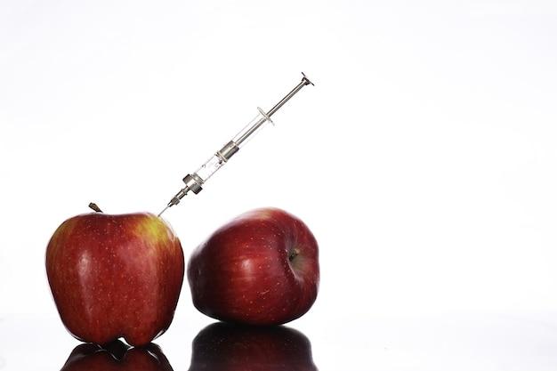 Aliments génétiquement modifiés, pomme pompée avec des produits chimiques à partir d'une seringue