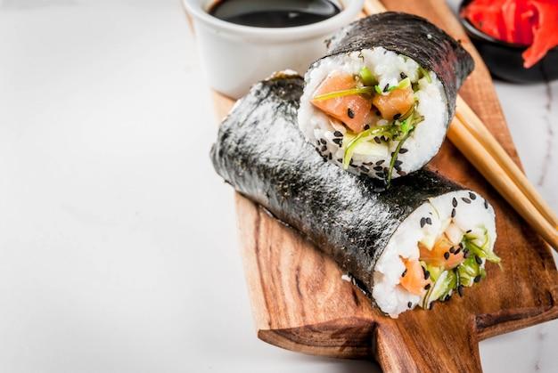 Aliments hybrides tendance. cuisine japonaise, asiatique. sushi-burrito, sandwich au saumon, wakame hayashi, daikon, gingembre mariné, caviar rouge. sur une table en marbre blanc, avec des baguettes et de la sauce soja. espace copie