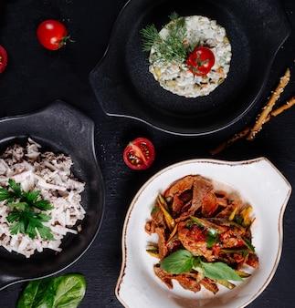 Aliments mélangés dans des casseroles blanches et noires.