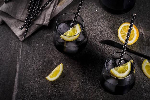 Aliments à la mode boissons rafraîchissantes d'été concept de désintoxication et de régime limonade noire avec du jus de citron au charbon et du citron