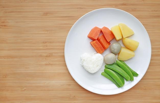 Aliments pour bébés bouillis (carotte, oeuf, pomme de terre, riz et pois sucré) en plaque blanche