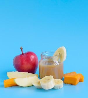 Aliments pour bébés faits à la main avec des pommes, des bananes, des poires et de la citrouille dans des bocaux en verre