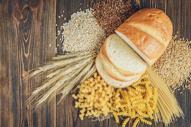 Les aliments riches en glucides sur fond de bois. pain, pâtes, orge perlé et avoine.