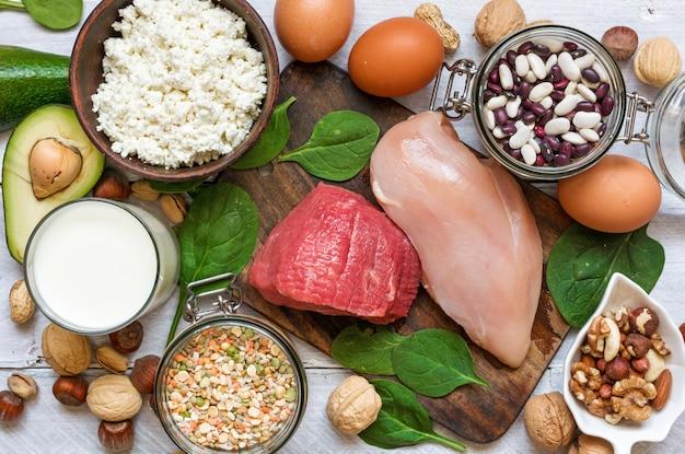 Aliments riches en protéines - poulet, viande, épinards, noix, œufs, haricots et fromage.