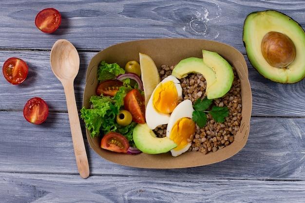 Aliments sains dans des emballages alimentaires écologiques jetables. avоcado, œuf à la coque, tomates, olives, sarrasin