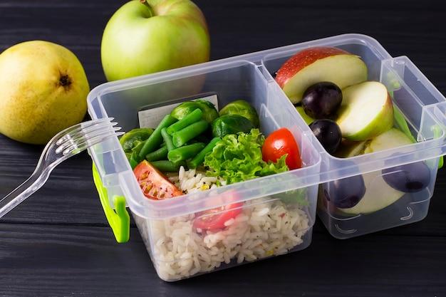 Aliments sains et diététiques dans une boîte à lunch. légumes et fruits, pommes, asperges, raisins, riz, tomates, laitue, dans un récipient en plastique.