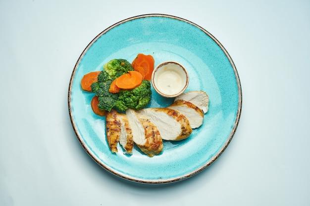 Aliments sains et diététiques - filet de poulet au four avec carottes bouillies et brocoli dans une plaque en céramique bleue isolée surface gris clair.