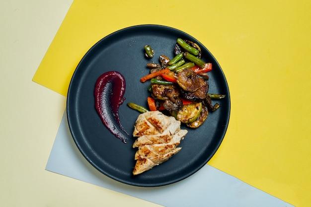 Des aliments sains et diététiques - filet de poulet grillé avec des légumes grillés dans une plaque en céramique noire sur une surface colorée close up