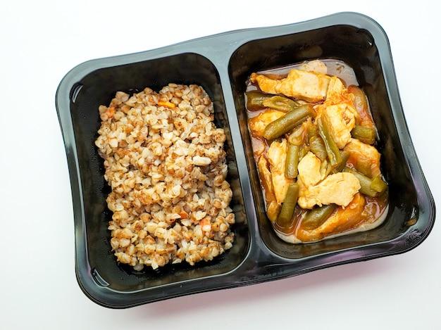Des aliments sains, du sarrasin et du poulet avec des haricots verts sur un mur isolé
