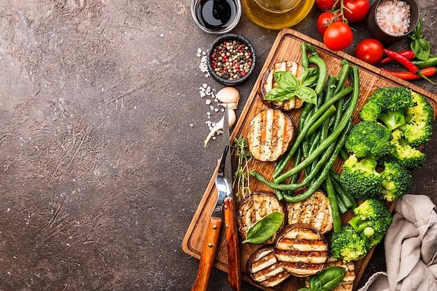 Des aliments sains légumes grillés sur une planche à découper sur une surface sombre, vue du dessus