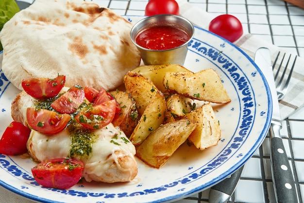 Des aliments sains pour le déjeuner: pomme de terre au four avec filet de poulet avec mozzarella et tomates cerises sur une plaque en céramique sur un tableau blanc. vue rapprochée
