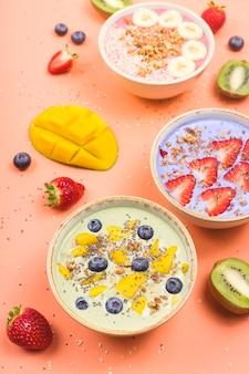 Des aliments sains végétariens à base de smoothies multicolores avec des allumettes et des baies sur une table rose vif