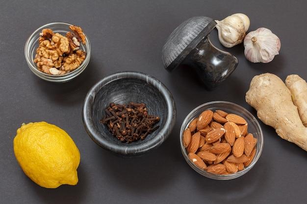 Aliments de santé pour le soulagement du rhume et de la grippe avec du citron, de l'ail, des amandes, du gingembre et des noix sur fond noir. vue de dessus. aliments qui stimulent le système immunitaire.