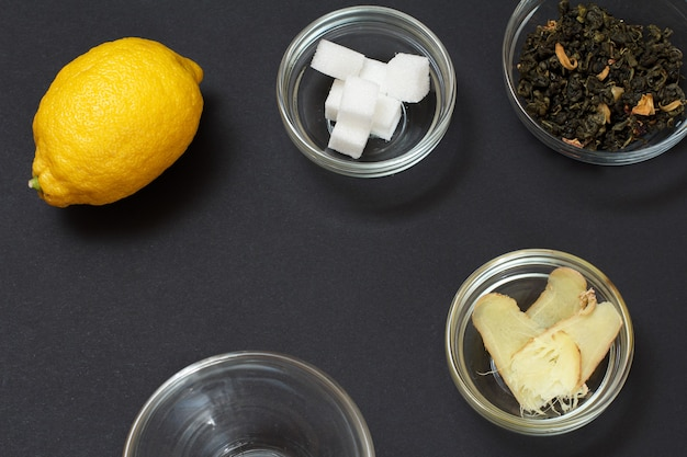 Aliments de santé pour le soulagement du rhume et de la grippe avec du citron, du gingembre et du thé vert sur une surface noire