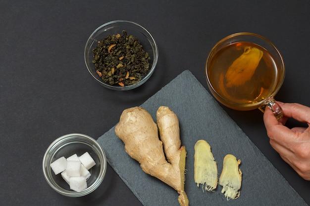 Aliments de santé pour le soulagement du rhume et de la grippe avec du gingembre et du thé sur une surface noire