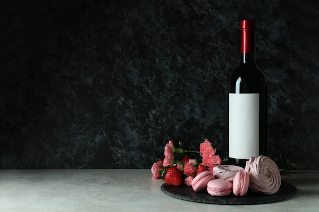 Aliments sucrés et bouteille de vin vierge sur fond noir smokey