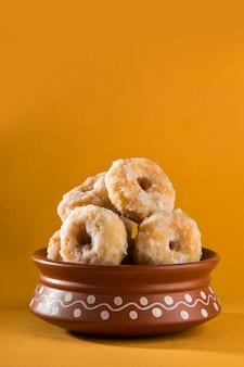 Aliments sucrés traditionnels indiens balushahi sur fond jaune