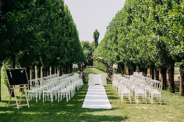 Allée de cérémonie de mariage vide avec tapis, arc rond et chaises en rangées