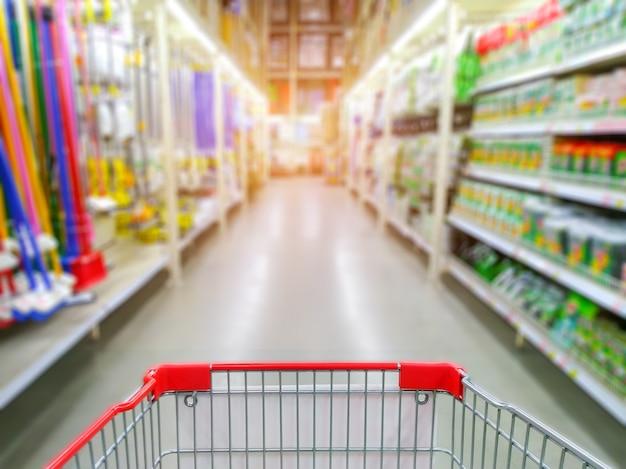 Allée de supermarché avec panier vide rouge