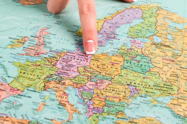L'allemagne dans l'atlas. le doigt d'une femme montre les frontières de l'allemagne. maison de la meilleure bière. membre de l'union européenne.