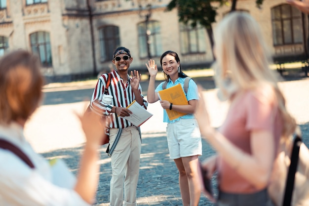 Aller dans des directions différentes. deux étudiants souriants agitant la main à leurs camarades de classe debout devant dans la cour de l'université.