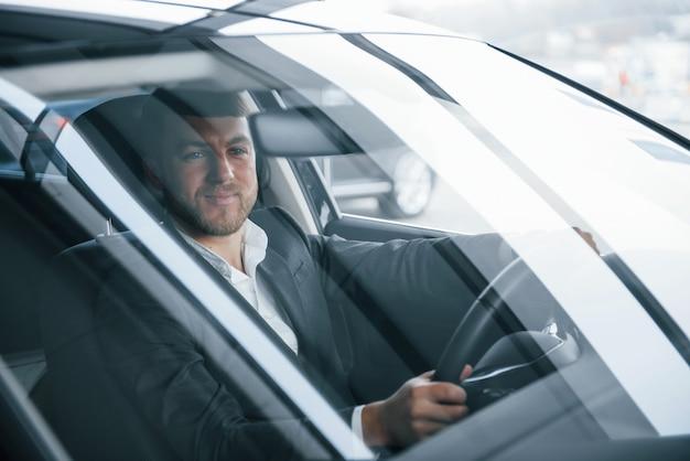 Où aller. homme d'affaires moderne essayant sa nouvelle voiture dans le salon automobile