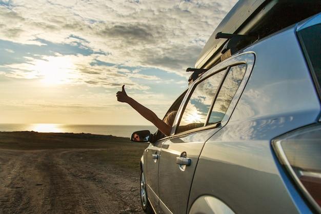 Aller à la mer en voiture. la fille tendit la main. pouce en signe de plaisir