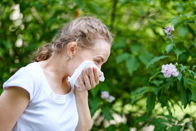 Allergie. femme se mouchant en se tenant près des fleurs dans un parc. femme, infection, éternuements