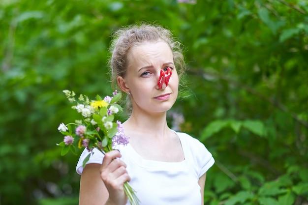 Allergie. une femme se serra le nez avec une pince à linge, pour ne pas éternuer du pollen des fleurs