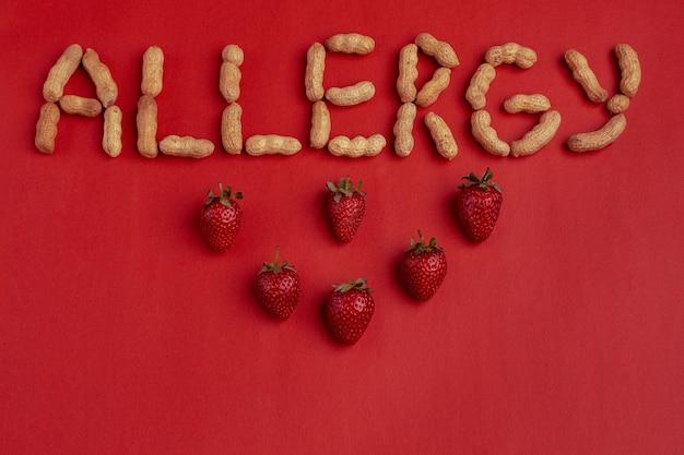 Allergie de mot signé avec des noix sur fond rouge. concept d'allergie aux fraises.