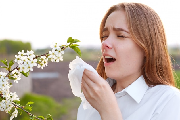 Allergie saisonnière. jolie jeune femme se mouche et éternue