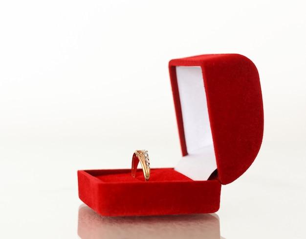 Une alliance, un cadeau dans une boîte rouge.